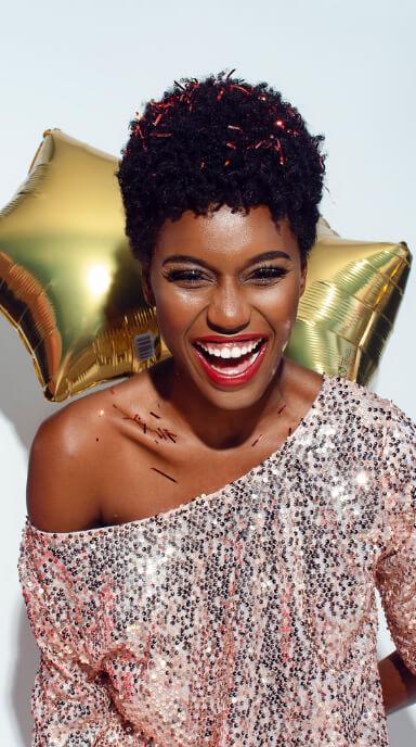 Mulher com sorriso largo segurando balões de estrela nas costas e com confetes na cabeça.