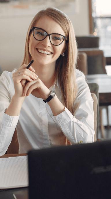 Mulher sorrindo com cotovelos sobre a mesa, mãos entrelaçadas e segurando uma caneta